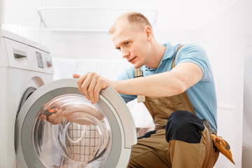 Handyman fixing washing machine