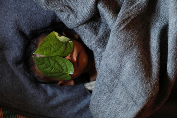 Leaves cover the face of Rohingya refugee Aziz after his body was brought back to family shelter at Balukhali refugee camp near Cox's Bazar