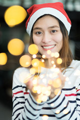 smiling asia woman wear santa hat holding party string lights with bokeh light at Christmas party,Holiday celebration concept,sparkling light decoration,make a wish