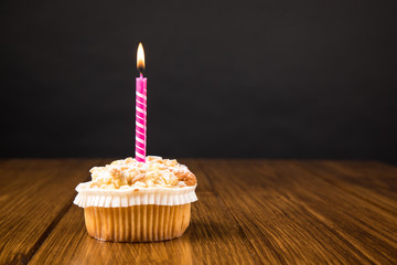 muffin with burning candle on a wooden background