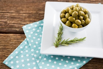 Marinated olives with rosemary on tray
