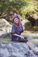 Karen woman smile sit on the rock in stream