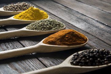 different spices in wooden spoons on a black wooden background
