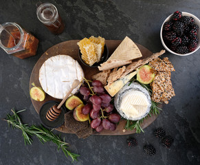 Seasonal cheese platter, with a variety of cheeses, fruit, honey, crackers and sprigs of rosemary.
