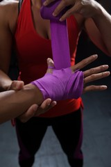 Trainer tying hand wrap on woman hand
