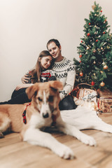 happy family in stylish sweaters and cute dog at christmas tree with lights and gifts. atmospheric festive moments. merry christmas and happy new year concept. space for text.
