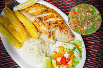Above view of fried fish served with side salad, rice, and yucca served in a white plate over a wooden table