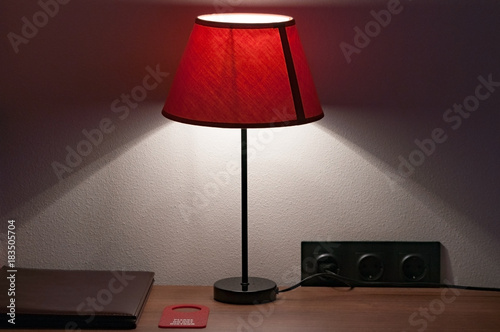 Intimate Atmosphere In The Hotel Room. Bedside Table On Which Lie The  Leather Folder Of