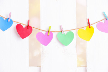 Colorful paper hearts on a string - Love concept with different colored paper hearts tied to a cord with wooden multicolored clips and a white wooden fence in the background.
