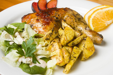 Chicken with potatoes  chips and salad on a white plate