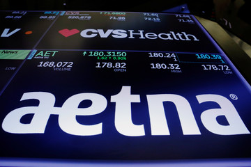 Logos of CVS and Aetna are displayed on a monitor above the floor of the New York Stock Exchange shortly after the opening bell in New York