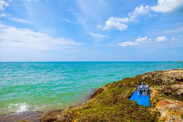Swim flippers, mask, snorkel on  rock moss beach sea and blue sky