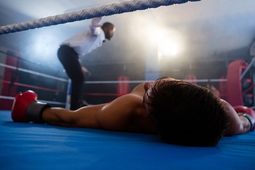 Unconscious boxer lying by referee in ring