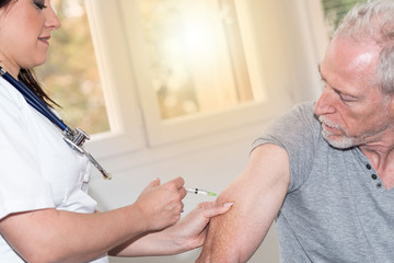 Female doctor giving vaccin injection to patient, light effect