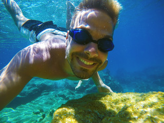 Underwater close photo of a young happy smiling tourist swimming in the turquoise sea under the surface near coral reef for summer vacation.