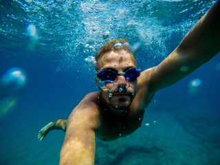 Underwater view of a young adventuristic attractive man swimming and enjoying at the sea for summer holidays while taking a selfie.