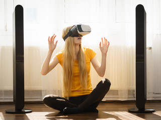 Girl wearing virtual reality goggles at home