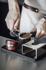 Hands of unrecognisable barman using espresso coffee maker filter.