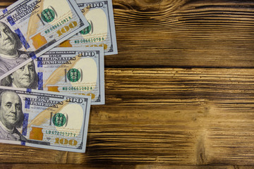 One hundred dollars bills on wooden desk