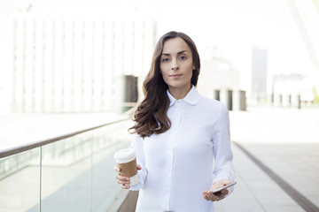 Modern smiling business woman walking with coffee and phone on the office outdoor.