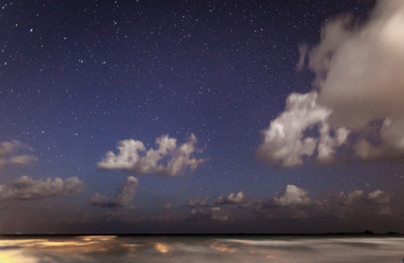 The night star sky over the ocean with the broken-off running clouds and a luminescence in the thickness of water. Long exposure.