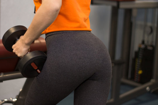 Woman dressed in sport wear working out in a gym lifting heavy weights