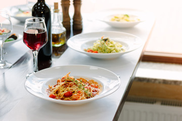 Table at italian restaurant served with traditional spaghetti pasta.