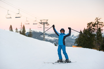 Girl enjoying ski holiday standing on the snowy mountain and raised her hands up. Woman at ski resort wearing helmet, blue ski suit and goggles.