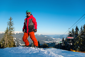 Full length shot of a smiling snowboarder standing on the slope in the mountains, looking to the camera in the evening at winter ski resort Bukovel, ski lift on the background copyspace recreation