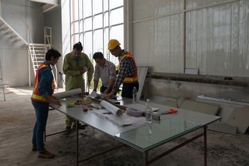 Engineer group asia and worker meeting, discussion with construction on site work in friendly atmosphere joking and having fun during working process.