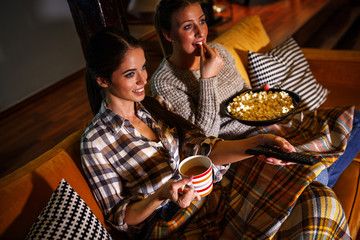 Two female best friends sitting at home on pleasant  evening and watching a movie .
