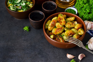 Young fried potatoes with garlic and dill on a black background