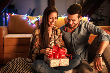Young woman opens a gift which she got from her husband.Anniversary concept.