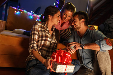Young woman opens a gift which she got from her friends.Celebration concept.