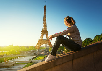 girl looking at the Eiffel tower in sunrise time, Paris