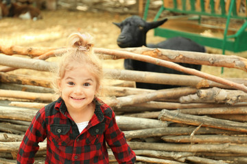 Cute little girl near enclosure with goats on farm