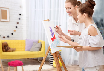 Little girl with mother painting boat at home