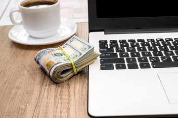 stack of dollar, cup of coffee and laptop on desk