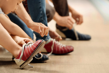 Family changing shoes in bowling club