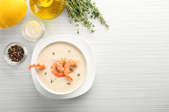 Composition with yummy shrimp cream soup on wooden table