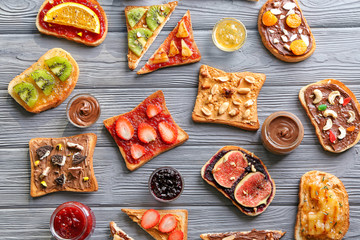 Toasts with various delicious toppings on wooden background