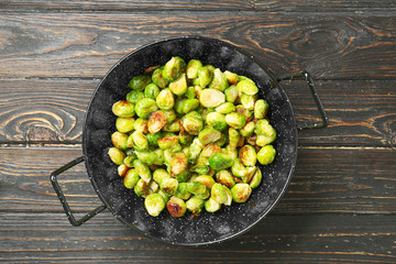 Frying pan with roasted brussel sprouts on wooden background
