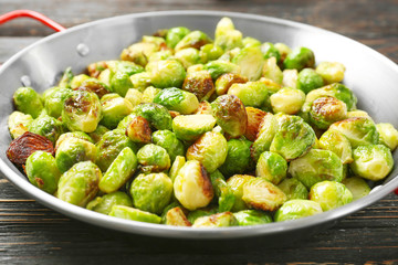 Frying pan with roasted brussel sprouts on table, closeup