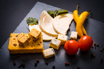 Cheese with mold, cherry tomatoes, basil and melissa greens, red hot pepper on a stone tray on a dark gray background