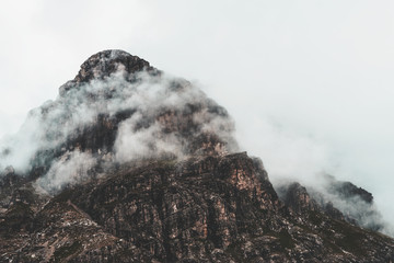 Fog shrouded rugged mountain peak and landscape