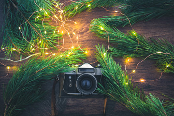 The old camera on a wooden background with Christmas tree branches and lights.