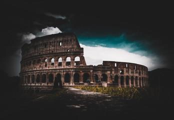 Colloseum amphitheater in Rome with grassy field
