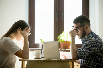 Stress at work: millennial businessman and businesswoman feeling confused and frustrated in office. Coworkers having headache, worrying about problems and failure in job