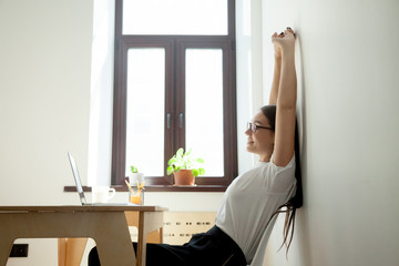 Break at work: female worker stretching hands above head at workplace. Beautiful millennial woman sitting at table in office and relaxing. Simple exercises to relieve stress, office gymnastics concept