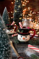 Hot chocolate in smiling snowman mugs in Christmas setting